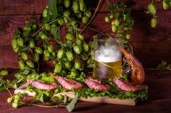 Bier mit Garnelen und Salat auf einem Holztisch Stockfoto