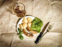 Bier mit gegrillten Würsten und gebratener Kartoffel Abbildung der roten Lilie Lizenzfreies Stockbild