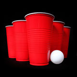 Bier pong. Rode plastic koppen en pingpongbal over zwarte Stock Fotografie