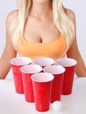 Bier pong. Rote Plastikschalen mit Klingeln pong Ball und blondem Mädchen im sexy Trägershirt Lizenzfreie Stockfotos