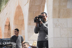 Bier-Sheva, ISRAËL - Maart 5, 2015: Cameraman op het werk Het schieten van prestaties tegen de achtergrond van het gebouw met bog Royalty-vrije Stock Foto