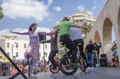 Bier-Sheva, ISRAËL - Maart 5, 2015: De jongens en de meisjes presteerden op fietsen met één wiel op de straatscène - Purim Stock Foto