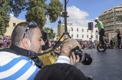 Bier-Sheva, ISRAËL - Maart 5, 2015: De mannelijke fotograaf bij de scène met een tiener op een één-fiets rijdt - Purim Stock Foto's