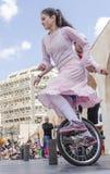 Bier-Sheva, ISRAËL - Maart 5, 2015: Het meisje in een roze kleding op een fiets met één wiel - Purim Royalty-vrije Stock Fotografie
