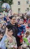 Bier-Sheva, ISRAËL - Maart 5, 2015: Jonge moeder met twee zonen in Carnaval-kostuums in de menigte - Purim Royalty-vrije Stock Afbeeldingen