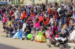 Bier-Sheva, ISRAËL - Maart 5, 2015: Kinderen in Carnaval-kostuums met hun ouders op de straat in viering van Purim Stock Foto's