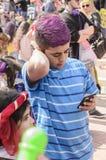 Bier-Sheva, ISRAEL - 5. März 2015: Jugendlichjunge mit dem purpurroten Haar färbte in einem blauen gestreiften Hemd mit Handy - P Lizenzfreie Stockbilder