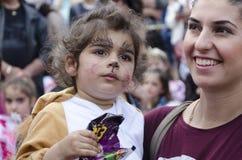 Bier-Sheva, ISRAEL - 5. März 2015: Porträt einer jungen Mutter mit einem Kind mit Make-upkatze mit großen Augenbrauen - Purim Stockfotografie