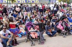 Bier-Sheva, ISRAEL - 5. März 2015: Eltern mit Kinderpublikum - sitzen Sie und passen Sie die Leistung auf der Straße auf - Purim Lizenzfreies Stockbild
