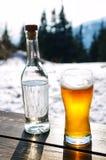 Bier und Flasche des harten Getränks auf Holztisch in den Winterbergen Stockfoto