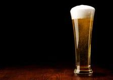 Bier und Glas auf einer schwarzen und hölzernen Tabelle Stockfotos