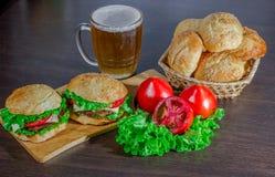 Bier und selbst gemachte Burgerbrötchen mit frischen Salatbestandteilen der Rindfleischpastetchen Stockfoto