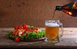 Bier von einer Flasche gießen herein einen transparenten Becher Stockbild