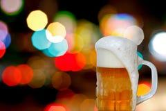 Bierbecher mit Schaum und bokeh Stockfotografie