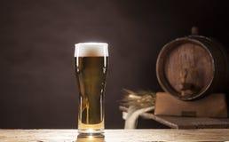 Bierfaß mit dem Bierkrug auf braunem Hintergrund Lizenzfreies Stockfoto