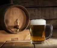 Bierfaß mit dem Bierkrug auf hölzernem Hintergrund Stockbild
