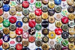 Bierflasche bedeckt Hintergrund, Mischung von verschiedenen Weltmarken mit einer Kappe stockfotos