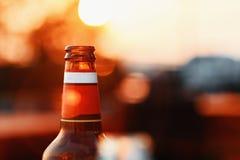 Bierflasche gegen Sommer-Himmel bei Sonnenuntergang auf undeutlichem Hintergrund mit Blendenfleck Lizenzfreie Stockbilder