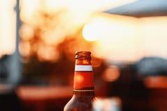 Bierflasche gegen Sommer-Himmel bei Sonnenuntergang auf undeutlichem Hintergrund mit Blendenfleck Lizenzfreies Stockfoto
