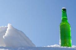 Bierflasche im Schnee Stockfotos