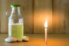 Bierflasche und Feuer von Kerzen setzten an Holz mit hölzernem Hintergrund unter Verwendung der Tapete für Partei nachts Stockbild