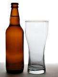 Bierflasche und leeres Glas Stockfotografie