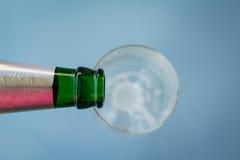 Bierflaschehals über leerem Glas Stockbild