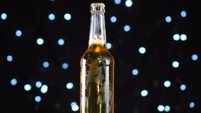 Bierflaschenahaufnahme Helles Bier in der Flasche gedreht über schwarzen Hintergrund stock video footage