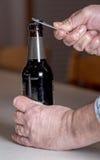 Bierfles die door een mens worden geopend royalty-vrije stock fotografie