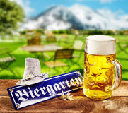 Biergarten or Beer Garden sign for Oktoberfest. Lying on a rustic outdoors wooden table at a tavern with a full frothy glass mug of beer and hat with a stock images