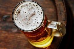 Bierglas auf hölzernem Fass Stockbild