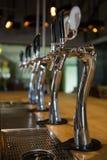 Bierhähne in der Reihe an der Bar Stockbild
