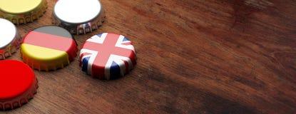 Bierkappen mit Großbritannien- und Deutschland-Flaggen auf hölzernem Hintergrund, Kopienraum, Fahne Abbildung 3D Lizenzfreie Stockfotografie