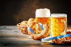 Bierkrüge und Brezeln auf einem Holztisch Oktoberfest Bierfestival stockbilder