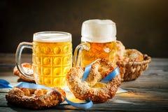 Bierkrüge und Brezeln auf einem Holztisch Oktoberfest Bierfestival lizenzfreie stockfotografie