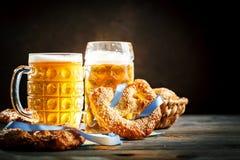 Bierkrüge und Brezeln auf einem Holztisch Oktoberfest Bierfestival stockfotografie