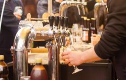 Bierkranen en vage mensen in het festival van het straatvoedsel stock afbeelding