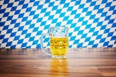 Bierkrug auf hölzernem Brett vor bayerischer Flagge Lizenzfreie Stockfotos