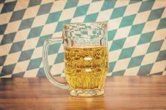 Bierkrug auf hölzernem Brett vor bayerischer Flagge Lizenzfreies Stockfoto