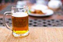 Bierkrug mit Bier auf einer Tabelle Stockfotografie