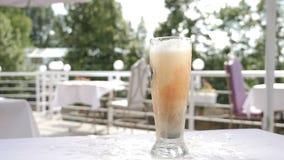 Bierspritzen Biergetränkeumhüllung Kleine flass mit der dunklen alkoholischen Flüssigkeit, die in Glas mit Bier fällt Langsame Be stock video footage