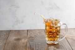 Bierspritzen im Glas auf einem hölzernen Hintergrund Lizenzfreie Stockfotos