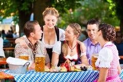 In Biertuin - vrienden op een lijst met bier Stock Fotografie