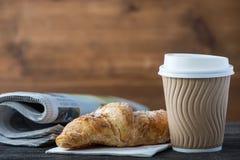 Bierze oddaloną kawę, świeżego croissant i gazeta Zdjęcia Royalty Free