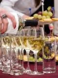 Bieten - den Wein heraus gießen Stockbilder