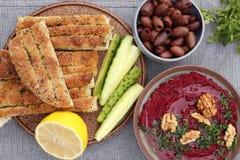Bietenhummus met olijven en brood stock foto