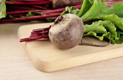 Bietola con le foglie e le barbabietole su minestra sul tagliere Fotografie Stock