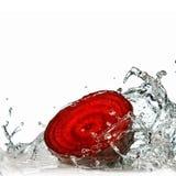 Bietola rossa con la spruzzata dell'acqua isolata su bianco Immagini Stock
