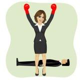 Bifall för framgångaffärskvinna med lyftta armar som framme bär boxninghandskar av mannen som ligger på golv Arkivfoto