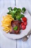 Bife, batatas fritas e vegetais grelhados Imagem de Stock